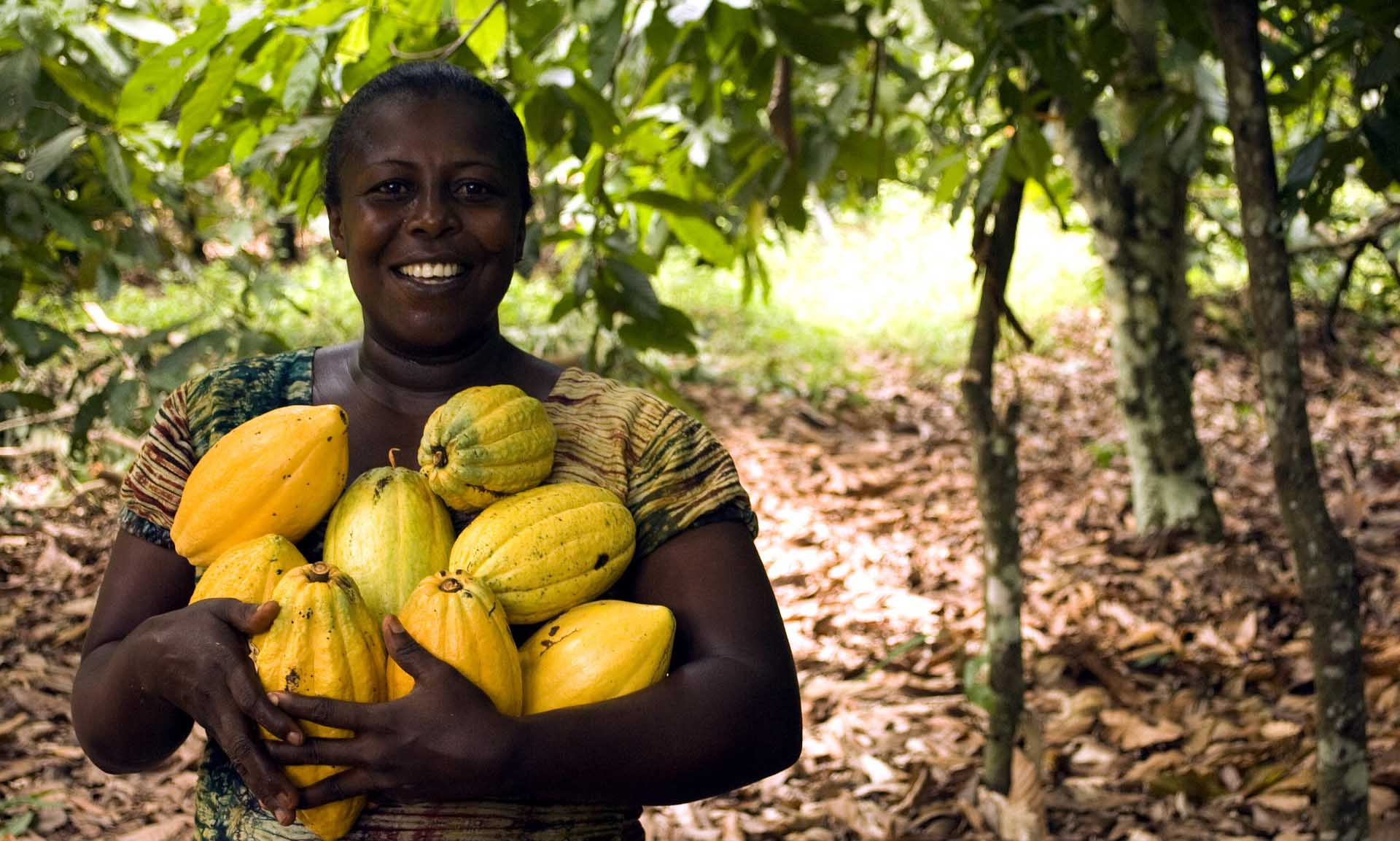smiling woman holding cacao pods